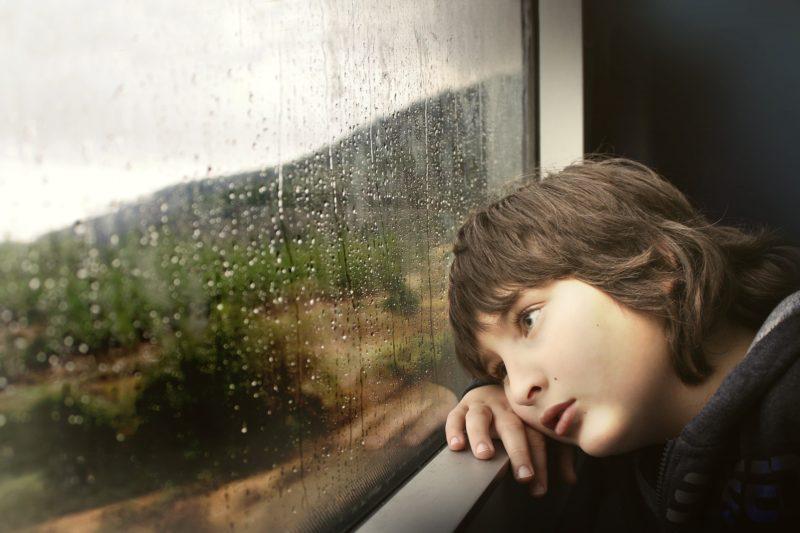 窓から外を眺めて黄昏る少年